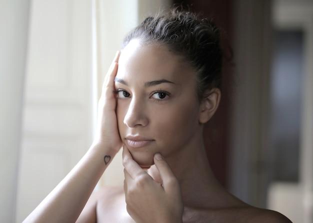 Portret młodej dziewczyny atrakcyjne z rękami na twarzy, pozowanie przed oknem
