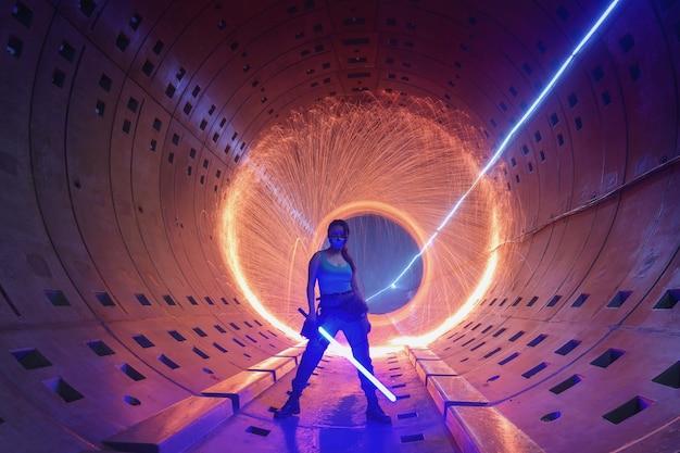 Portret młodej dziewczyny bawi się oświetleniem w podziemnym tunelu do metra. fotografia nocna