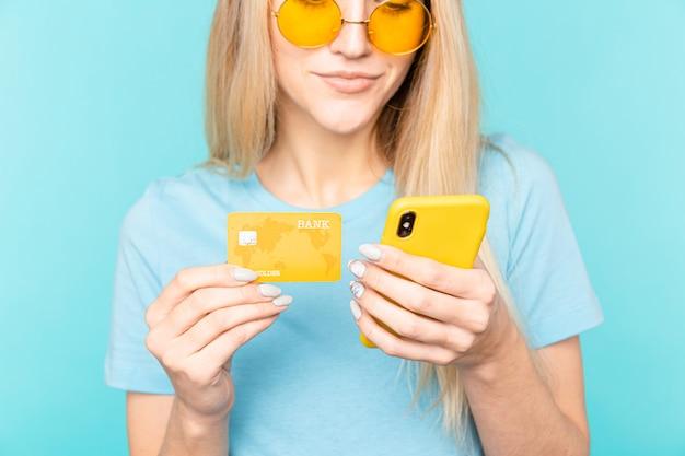 Portret młodej dziewczyny blondynka, trzymając telefon komórkowy i plastikową kartę kredytową na niebieskim tle