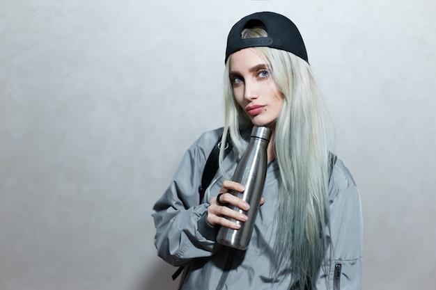Portret młodej dziewczyny blondynka w ręku ze stalową butelką thermo eco