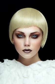 Portret młodej dziewczyny blondynka z modnym makijażem, patrząc prosto w kamerę