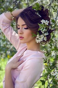 Portret młodej dziewczyny brązowe włosy z makijażem w wiśni sakura różowy, biały w białej sukni