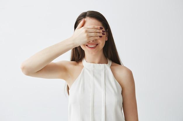 Portret młodej dziewczyny brunetka obejmujących oczy ręką uśmiecha się.