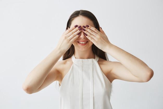Portret młodej dziewczyny brunetka obejmujących oczy z rękami uśmiechając się.
