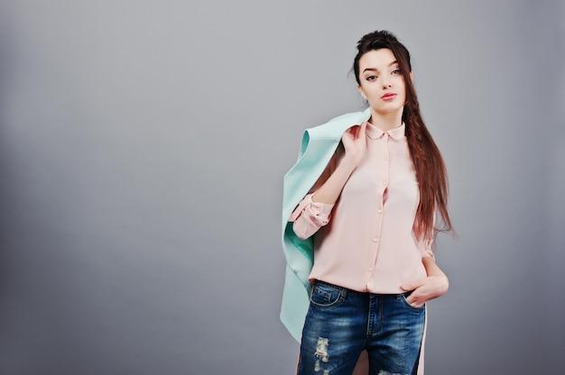 Portret młodej dziewczyny brunetka ubrana w różową bluzkę, turkusową kurtkę, zgrywanie dżinsy