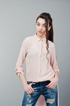 Portret młodej dziewczyny brunetka ubrana w różową bluzkę, zgrywanie dżinsy