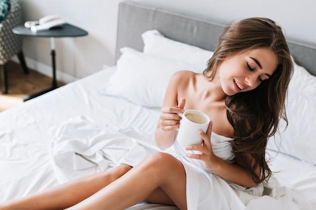 Portret młodej dziewczyny brunetka z niegrzecznymi nogami i ramionami na białym łóżku. trzyma kubek, ma zamknięte oczy, wygląda na zadowoloną.