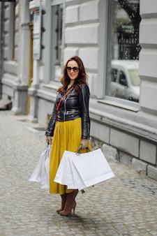 Portret młodej dziewczyny całkiem stylowe trzymając torby na zakupy i nie mogę się doczekać w dobrym nastroju. idealne zakupy.