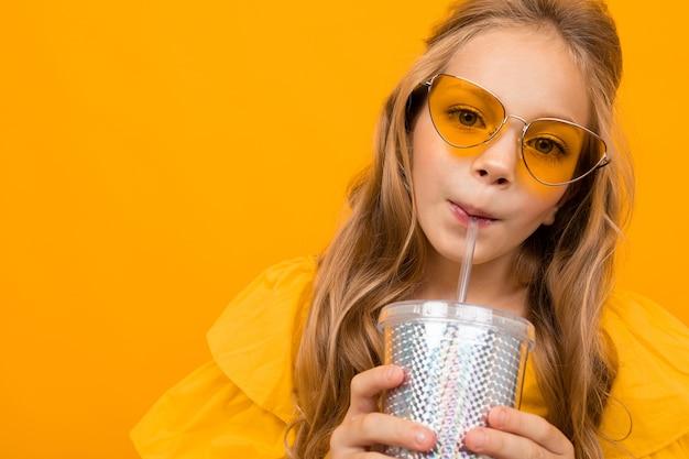 Portret młodej dziewczyny caucaian z długimi jasnymi włosami w żółtych okularach pije sok i uśmiecha się