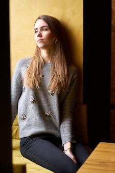 Portret młodej dziewczyny dość zamyślony z długimi włosami i naturalny makijaż w kawiarni.