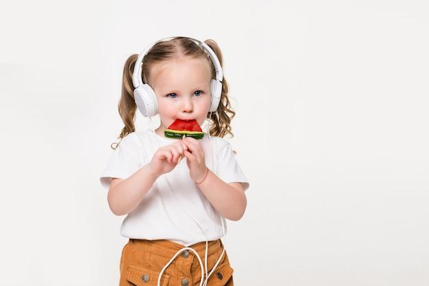 Portret młodej dziewczyny dziecko w zestawie słuchawkowym jeść cukierki