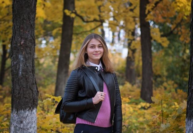 Portret młodej dziewczyny europejskiej w jesiennym parku z żółtymi liśćmi