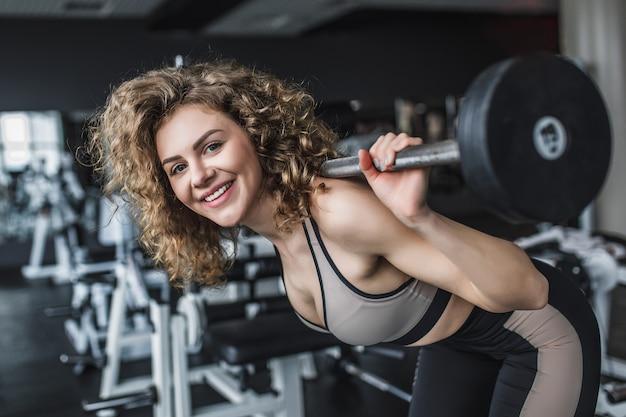 Portret młodej dziewczyny fitness robi przysiady ze sztangą na siłowni
