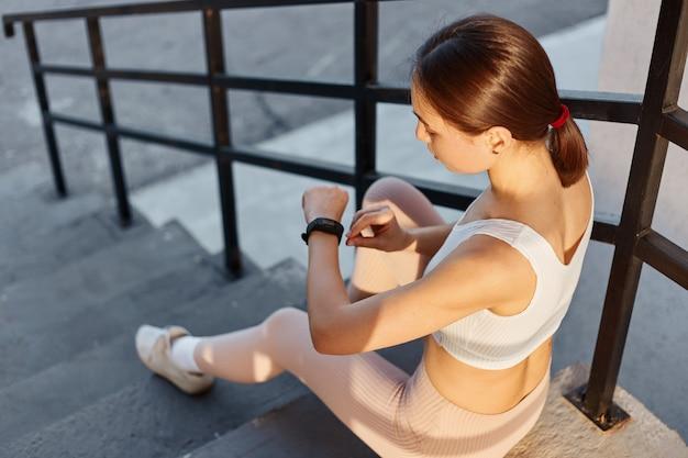 Portret młodej dziewczyny fitness, siedzącej na schodach na zewnątrz i sprawdzającej ilość spalonych kalorii po treningu, ciemnowłosa kobieta w białej bluzce i beżowych legginsach.