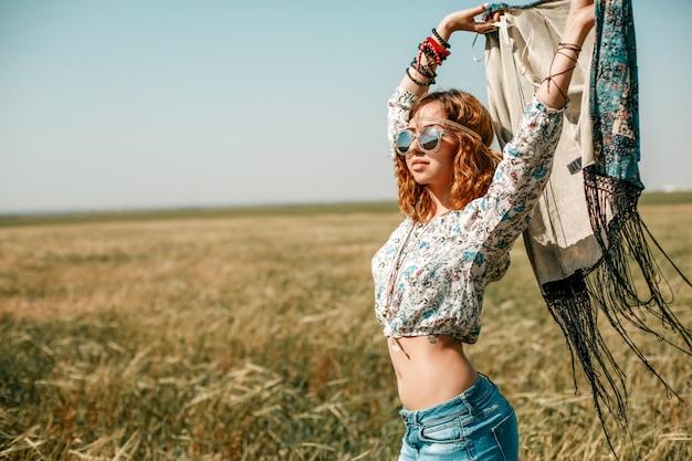 Portret młodej dziewczyny hippie na polu pszenicy