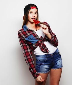 Portret młodej dziewczyny hipster pozuje na szarym tle z czerwonym lizakiem