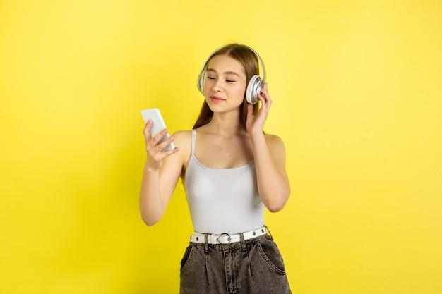 Portret młodej dziewczyny kaukaski na białym tle na żółty studio