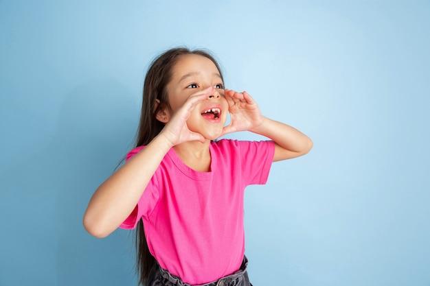 Portret młodej dziewczyny krzyczącej odizolowanej na niebieskiej ścianie studia
