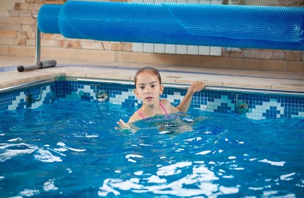 Portret młodej dziewczyny, która uczy się pływać w basenie
