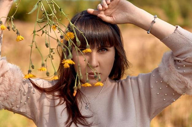 Portret młodej dziewczyny, która ukrywa połowę twarzy w kwiaty.