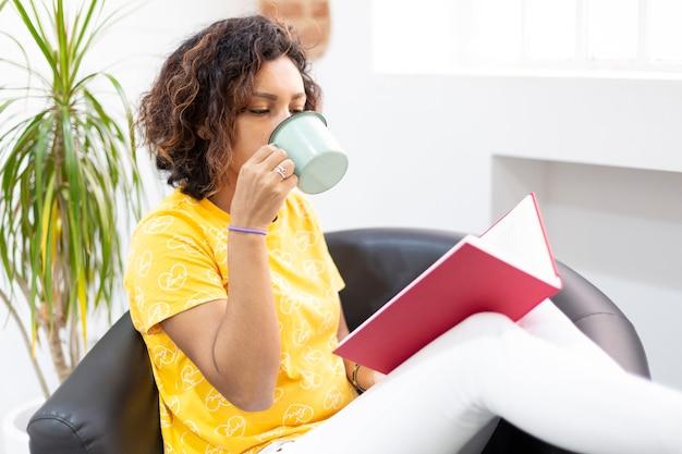 Portret młodej dziewczyny łacińskiej picia kawy siedząc i czytając książkę. miejsce na tekst.