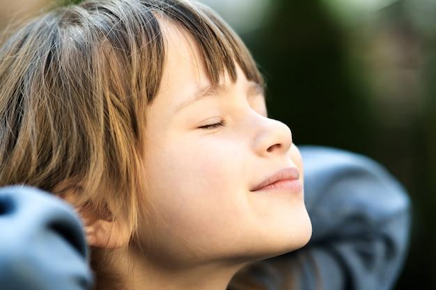 Portret młodej dziewczyny ładne dziecko z długimi włosami, ciesząc się ciepły słoneczny dzień w lecie na zewnątrz słodkie dziecko kobiece relaks na świeżym powietrzu na zewnątrz.