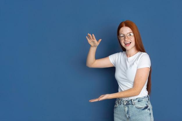 Portret młodej dziewczyny na białym tle na niebieskiej ścianie studia