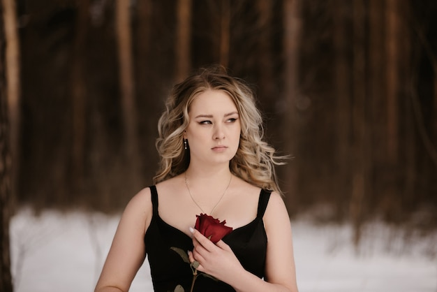 Portret młodej dziewczyny na obrazie ciemnej wiedźmy ze szkarłatną różą w dłoniach. obraz na halloween. mistycyzm.