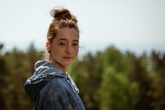 Portret młodej dziewczyny na tle przyrody, patrząc w kamerę