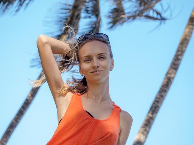 Portret młodej dziewczyny na wakacjach w pomarańczowej kamizelce i okularach przeciwsłonecznych na tropikalnej wyspie. wiejący silny wiatr z oceanu
