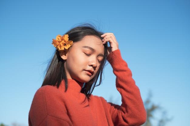Portret młodej dziewczyny nosić swater orang z kwiatem orang z niebieskim tle nieba.