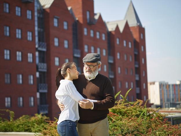 Portret młodej dziewczyny obejmując dziadka w parku