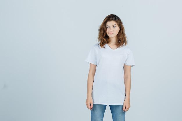 Portret młodej dziewczyny, patrząc na bok, zakrzywione usta w białej koszulce i patrząc zamyślony widok z przodu
