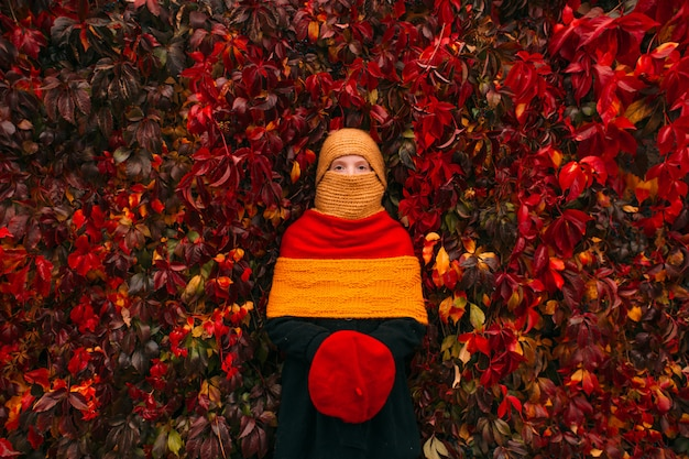 Portret młodej dziewczyny piegi na sobie kolorową sukienkę z maskaradą z maską i trzymając czerwony beret w dłoniach nad liśćmi bluszczu jesienią