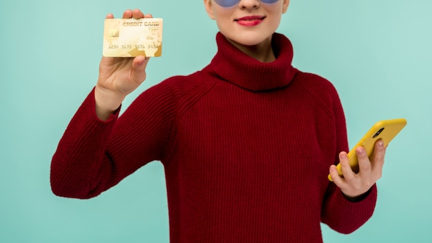 Portret młodej dziewczyny piękna pokazuje plastikową kartę kredytową, trzymając telefon komórkowy na białym tle na niebieskim tle