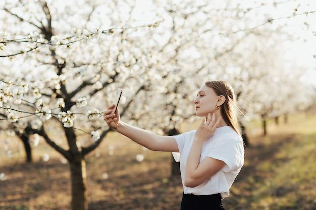 Portret młodej dziewczyny piękne, ciesząc się wiosną w parku i podejmowania selfie. kwitnące drzewa.