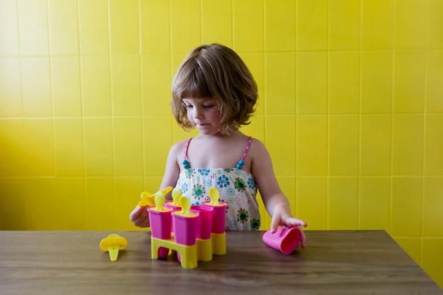 Portret młodej dziewczyny piękne dziecko grając z lodami w domu. szczęście i styl życia w pomieszczeniu. lato. żółta ściana