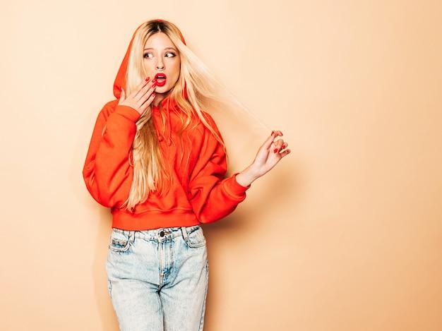 Portret młodej dziewczyny piękne hipster złe w modnej czerwonej bluzie z kapturem i kolczyk w nosie. zszokowany i zaskoczony