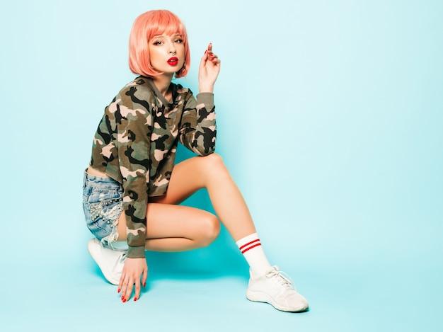 Portret młodej dziewczyny piękne hipster zły w modne czerwone letnie ubrania i kolczyk w nosie. seksowny beztroski uśmiechający się kobieta siedzi w studio w różowej peruce w pobliżu niebieską ścianą. pozytywny model zabawy