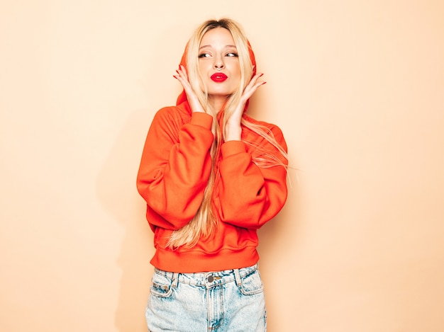 Portret młodej dziewczyny piękne hipster zły w modnej czerwonej bluzie z kapturem i kolczyk w nosie. seksowny beztroski blond kobieta pozowanie studio. pozytywny model zabawy