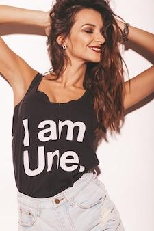 Portret młodej dziewczyny piękne uśmiechający się hipster w modne letnie czarne koszulki i spodenki jeans. seksowna beztroska kobieta odizolowywająca na bielu. model brunetka z makijażem i fryzurą