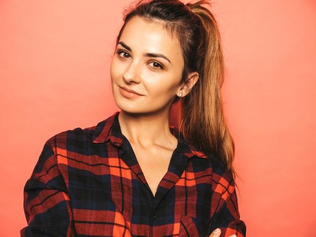 Portret młodej dziewczyny piękne uśmiechający się hipster w modne letnie kraciaste koszule i dżinsy ubrania. seksowna beztroska kobieta pozuje blisko menchii ściany w studiu. pozytywny model bez makijażu