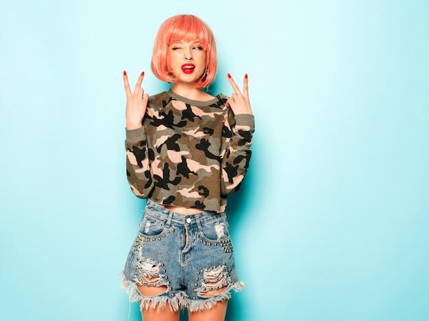 Portret młodej dziewczyny piękne złe hipster w modne jeansy spodenki i kolczyk w nosie. seksowna beztroska uśmiechnięta kobieta pozuje w studiu w różowej peruce. pozytywny model ma zabawę. pokazuje znak pokoju