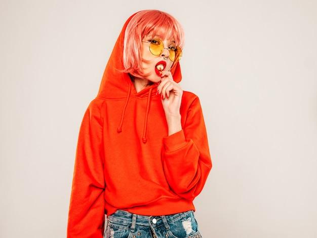 Portret młodej dziewczyny piękne złe hipster w modnej czerwonej letniej bluzie z kapturem i kolczyk w nosie. seksowny beztroski uśmiechający się blond kobieta pozowanie studio w peruce. model pozytywny lizanie okrągłe cukierki cukrowe