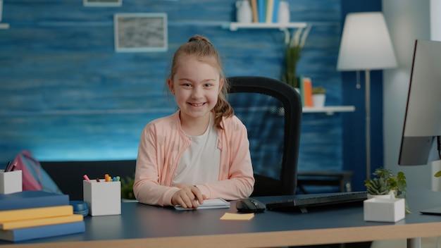Portret młodej dziewczyny piszącej na notebooku z uśmiechem pióra