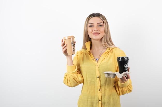 Portret młodej dziewczyny pozuje z filiżankami kawy na białym tle.