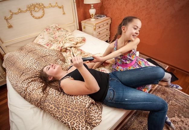 Portret młodej dziewczyny próbującej zabrać pilota telewizora od dorosłej siostry