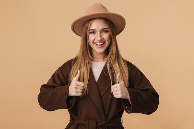 Portret młodej dziewczyny rasy kaukaskiej w kapeluszu i płaszczu, uśmiechający się i pokazujący kciuki w górę na beżowym tle
