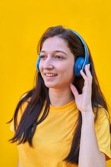 Portret młodej dziewczyny rasy kaukaskiej z długimi brązowymi włosami, żółta koszulka, słuchająca muzyki w niebieskich słuchawkach.