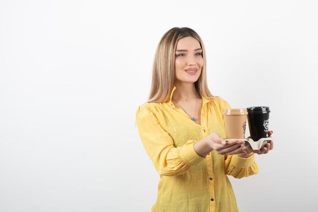 Portret młodej dziewczyny rozdaje filiżanki kawy na białym tle.